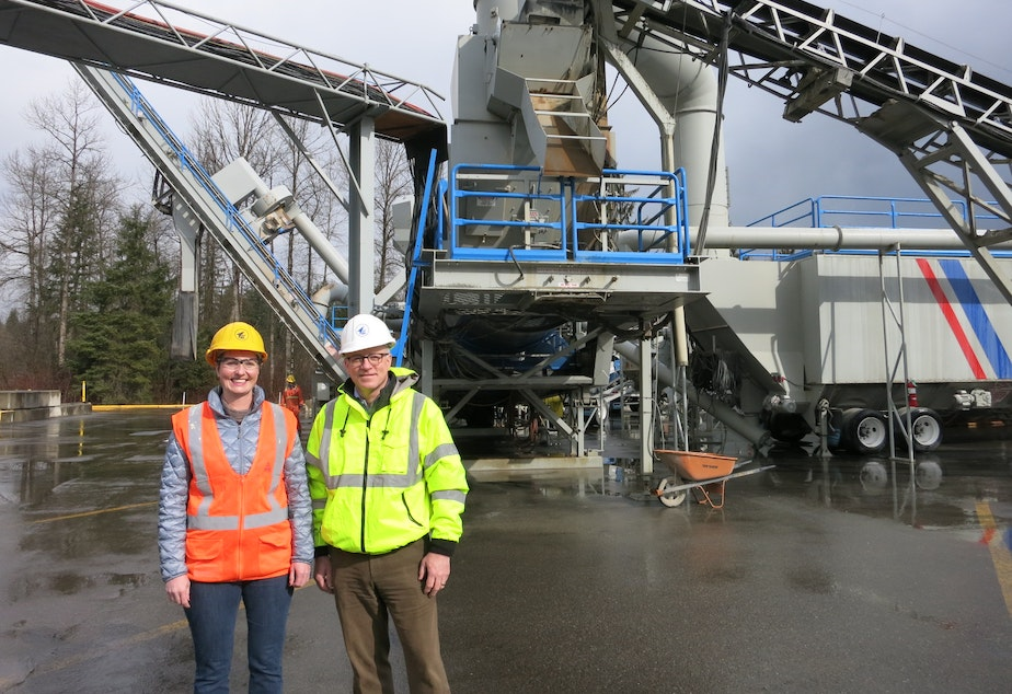 caption: Lakeside Industries environmental director, Karen Deal, and president, Mike Lee, pose in front of the company's asphalt plant in Covington. The company plans to relocate this equipment to a new site across from the Cedar River.