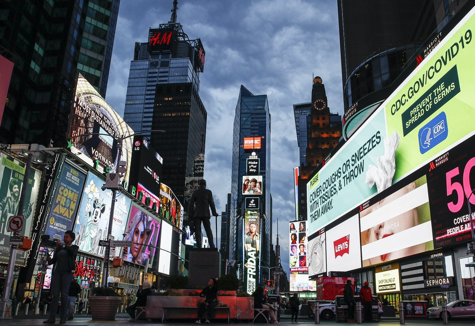 caption: A screen displaying messages concerning COVID-19 is seen in a sparsely populated Times Square in New York City on Friday. New York Gov. Andrew Cuomo has ordered all nonessential businesses to close by Sunday.