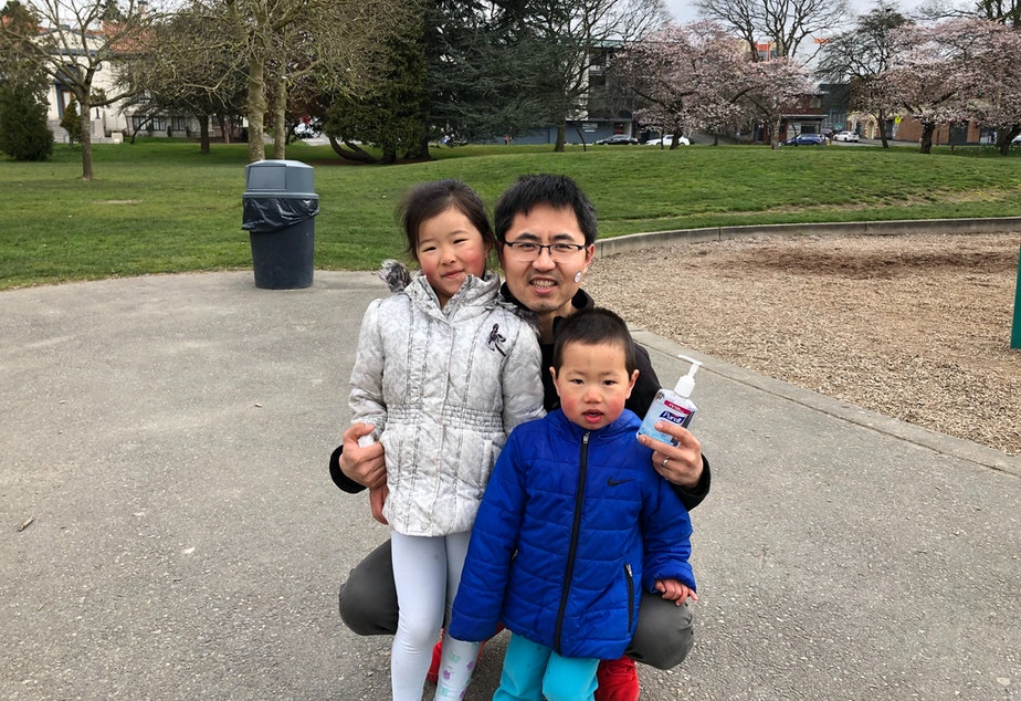 caption: Chao Duan keeps hand sanitizer close while his young kids explore Greenlake Park.