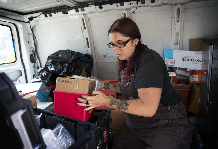 Lisa Al-Hakim, Director of Operations at the People's Harm Reduction Alliance, moves a box of syringes before doing outreach along Aurora Avenue on Monday, May 6, 2019, in Seattle.