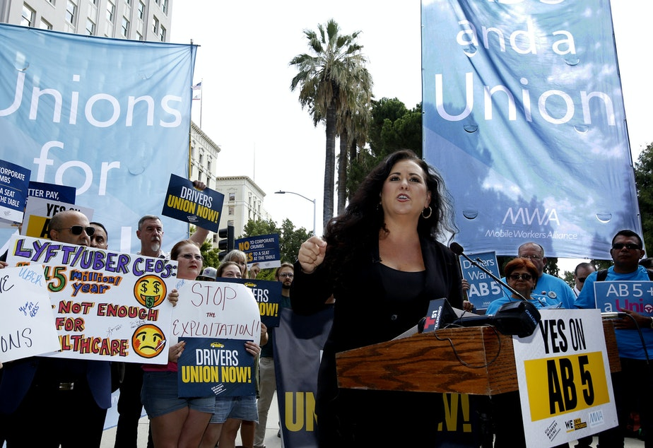 caption: Assemblywoman Lorena Gonzalez, D-San Diego, speaks at an August 28 rally in Sacramento, Calif., calling for passage of AB5 to limit when companies can label workers as independent contractors.