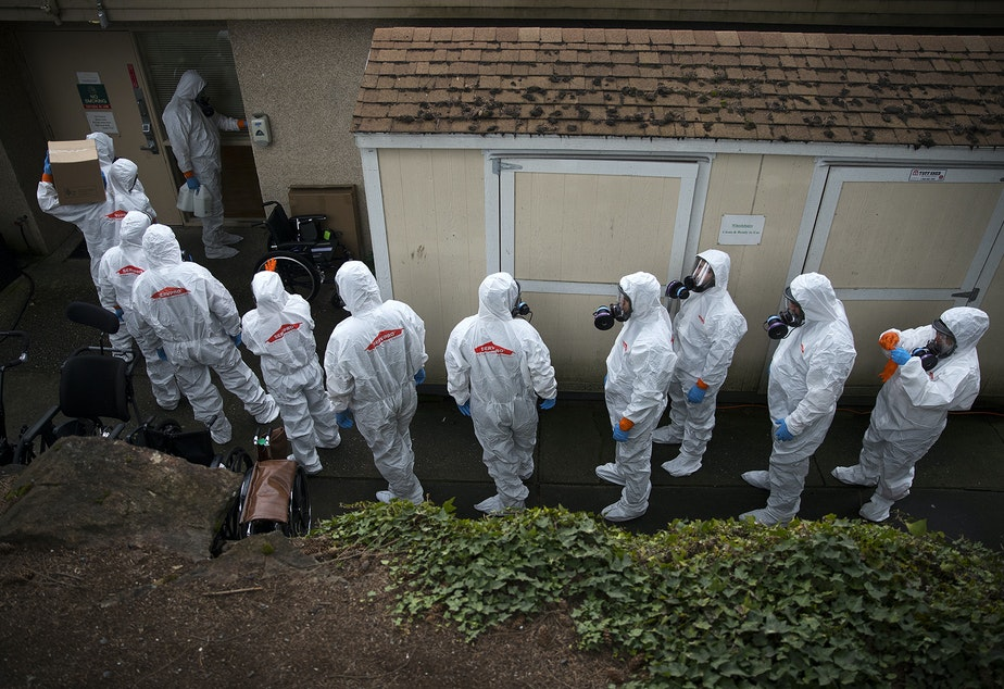 caption: Members of a Servpro cleaning crew line up before entering the Life Care Center of Kirkland, the long-term care facility at the epicenter of the coronavirus outbreak in Washington state, on Wednesday, March 11, 2020, in Kirkland.