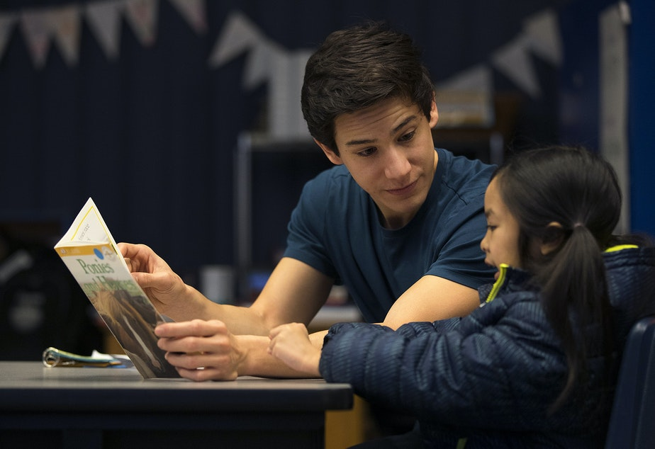 Volunteer Anthony Lee reads with Elizabeth Riff on Wednesday, January 24, 2018, at Sanislo Elementary School in West Seattle.