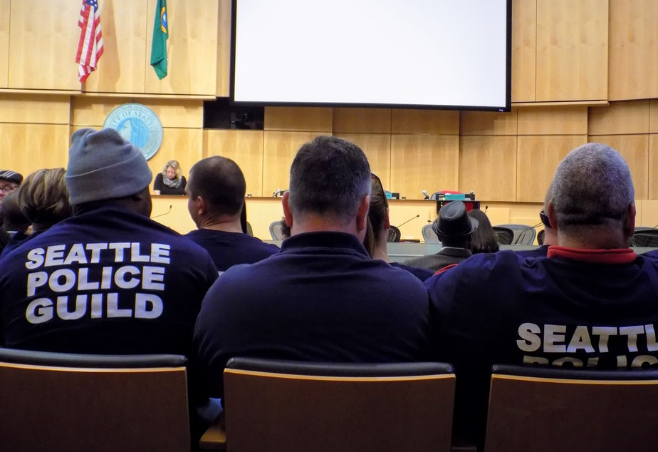 caption: Members of the Seattle Police Officers Guild packed the Council Chamber before a vote on a union contract between the guild and the city in 2018.