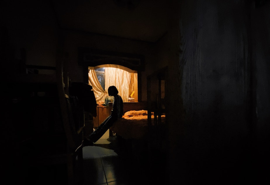 caption: An isolated person leans against their bed. They look outside a window through a small opening in the curtain.