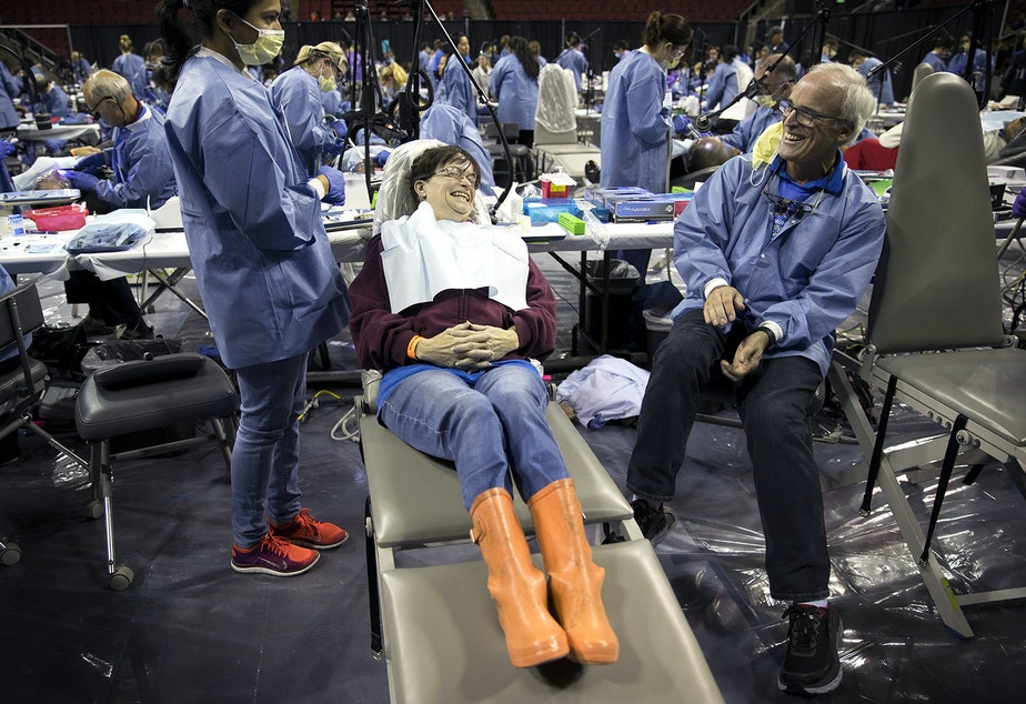 Donna Smith, center, laughs with Dr. Brad McPhee before getting a filling during the Seattle/King County Clinic on Thursday, October 26, 2017, at Key Arena. Tap to see more pictures.