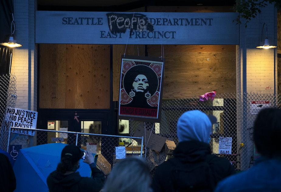 caption: A crowd gathers around the Seattle Police Department's East Precinct building at the intersection of 12th Avenue and East Pine Street on Saturday, June 13, 2020, inside the Capitol Hill Autonomous Zone, CHAZ, or Capitol Hill Occupied Protest, CHOP, in Seattle.