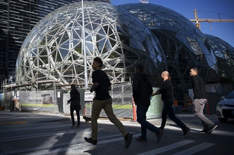 A group of people jog across Lenora Street in front of Amazon's biodomes, in Seattle.