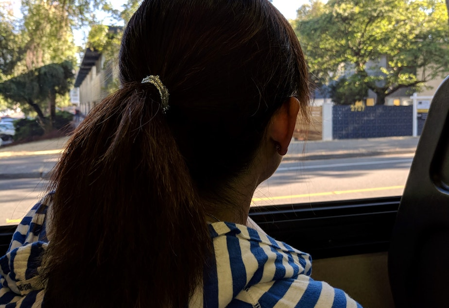 The author's mother, Jenny Huang, looks out of a bus window. In August 2016, she was slapped by a white woman for having her purse on the seat next to her on the bus as she napped.