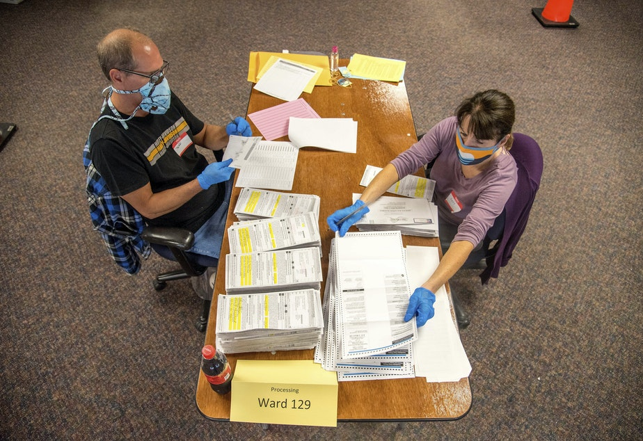 caption: In this photo provided by Wisconsin Watch, election workers Jeff and Lori Lutzka, right, process absentee ballots at Milwaukee's central count facility on Aug. 11, 2020. (Will Cioci/Wisconsin Watch via AP)