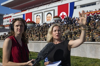 <em>All Things Considered</em> host Mary Louise Kelly (right) records a standup with producer Becky Sullivan at Kim Il Sung Square in Pyongyang ahead of a military parade marking the 70th anniversary of North Korea's founding.