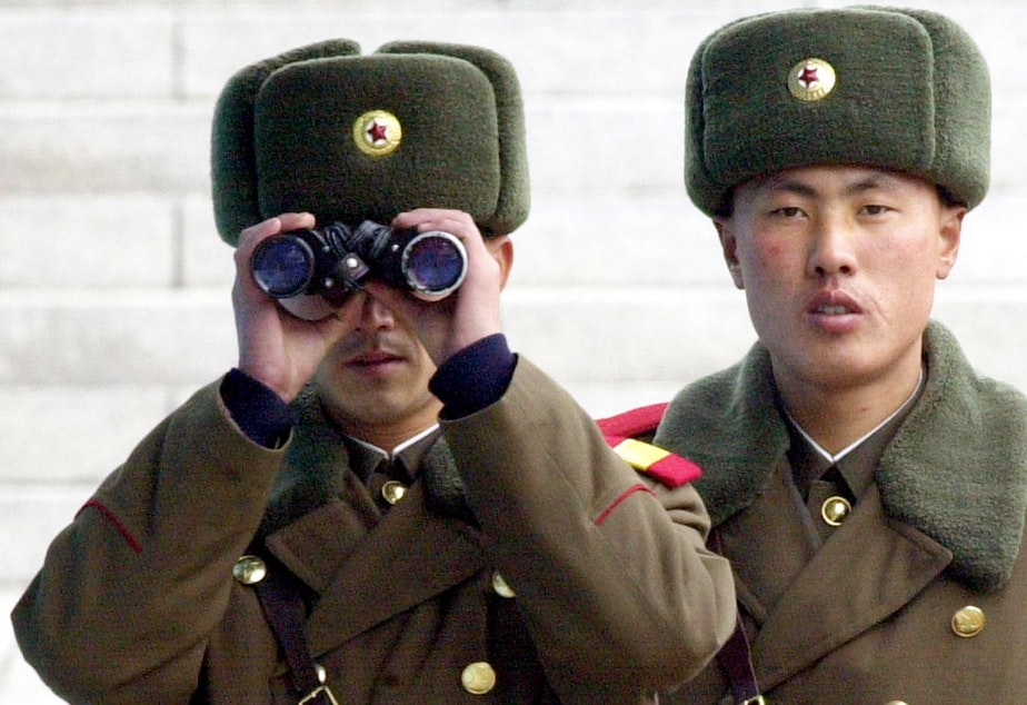 caption: A North Korean soldier looks at the southern side through a pair of binoculars at the border village of Panmunjom, north of Seoul, Wednesday, Feb. 26, 2003.
