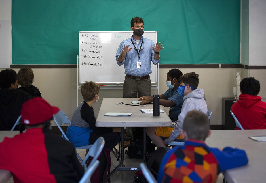 caption: Seattle School for Boys 6th-grade teacher Buck McKenna welcomes students back to the classroom on the first day of school, Monday, September 13, 2021, in Seattle.