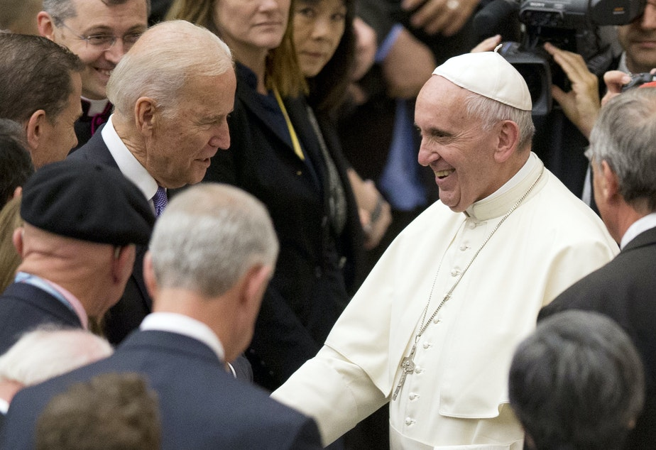 caption: Pope Francis shakes hands with Joe Biden, then vice president, at the Vatican, in 2016.