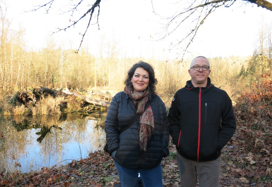 caption: KUOW listeners Meaghan Lodahl and Hans Reifenrath pose in front of the Cedar River. They live in Maple Valley and oppose a plan to relocate an asphalt plant across from where they're standing.