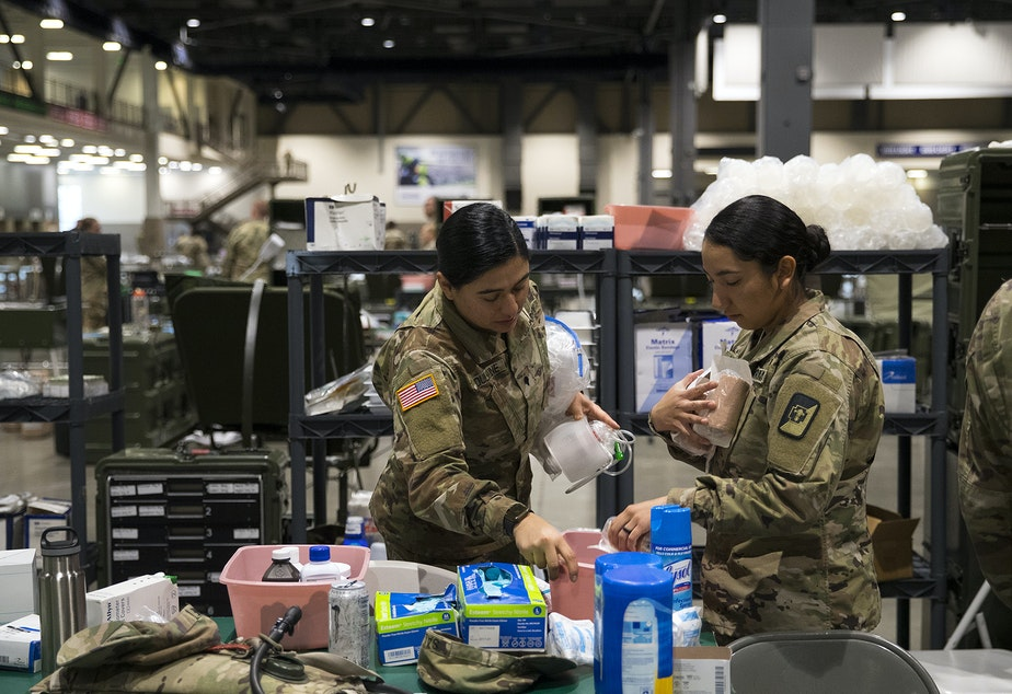 caption: U.S. Army soldiers store medical supplies on Tuesday, March 31, 2020, at the 250-bed military field hospital for non COVID-19 patients deployed at the CenturyLink Field Event Center in Seattle.