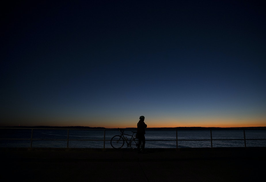 Eric Shalit watches the sunset during a bike ride on Tuesday, December 5, 2017, in West Seattle.
