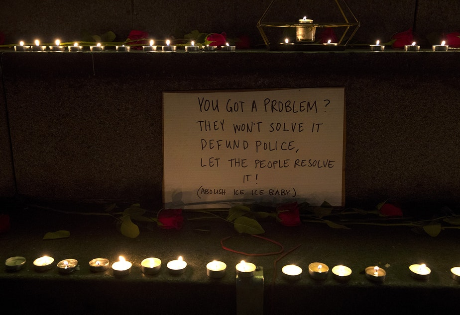 caption: A sign surrounded by lit candles is shown on Monday, October 26, 2020, during the 150th day of protests for racial justice in Seattle at Westlake Park.