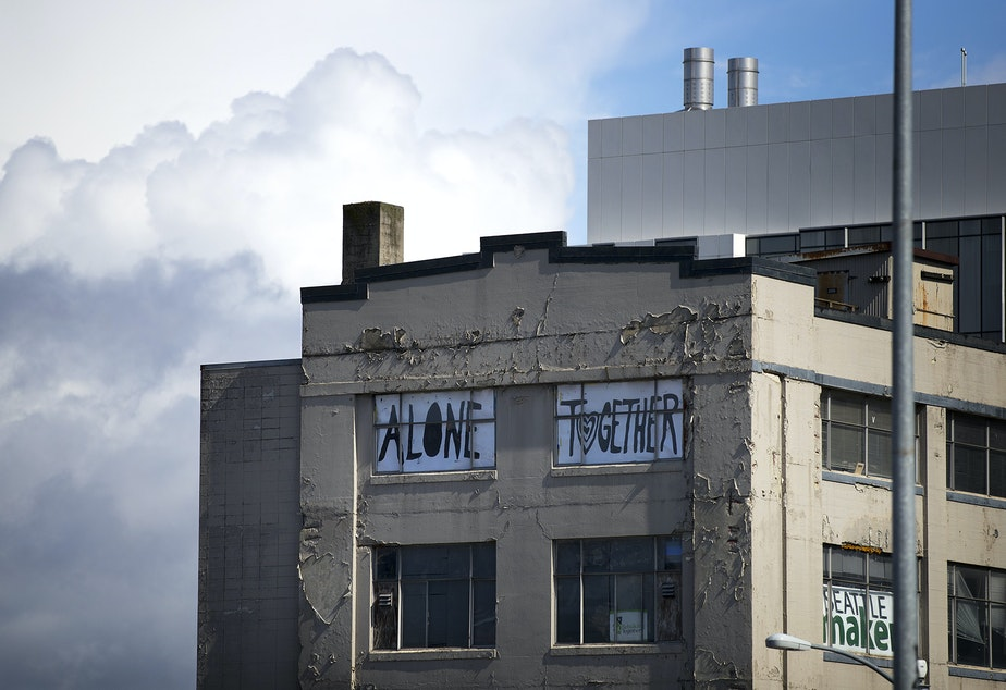 caption: 'Alone Together' reads a sign placed in the windows of a South Lake Union building, shown on Wednesday, March 25, 2020, in Seattle.