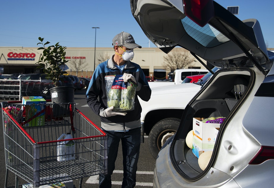 caption: Jon Hartley puts a bag of artichokes into the trunk of his car after shopping at Costco on Wednesday, March 18, 2020, in Seattle.