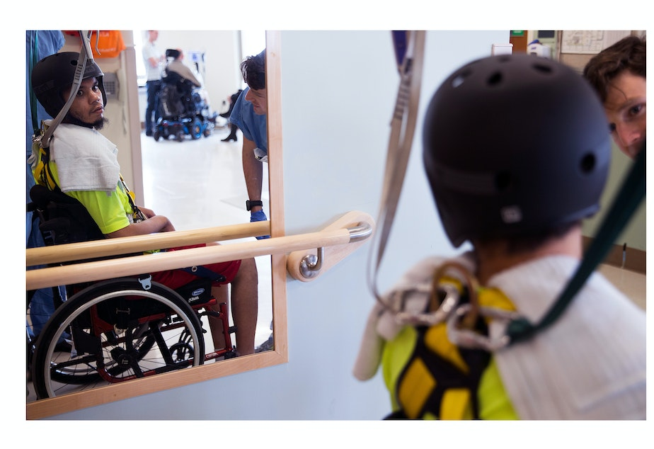 DaShawn Horne looks into a mirror while taking a break from learning to walk again, with his physical therapist, Trevor Bouten, right, on Tuesday, April 10, 2018, at Harborview Medical Center in Seattle. DaShawn was fastened into a rotating harness that was connected to the ceiling to learn to walk again. He needed help with walking, bathing, eating, brushing his teeth, and using the bathroom.