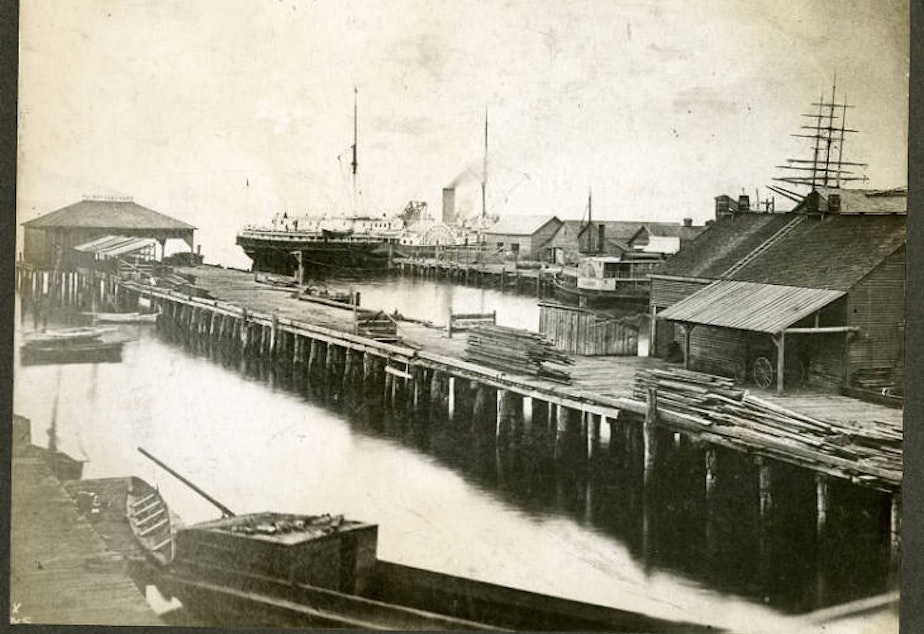 caption: The Seattle waterfront in 1880. This area was known as Yesler Wharf; it would today be one of the piers near the aquarium.