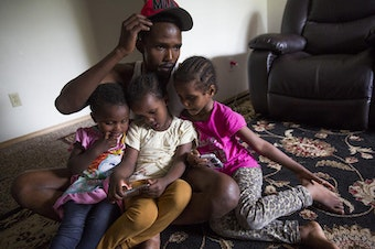 Osman Mohamed, of Somalia, and his three daughters, ages 2, 4 and 5 at their Seattle apartment in 2016.