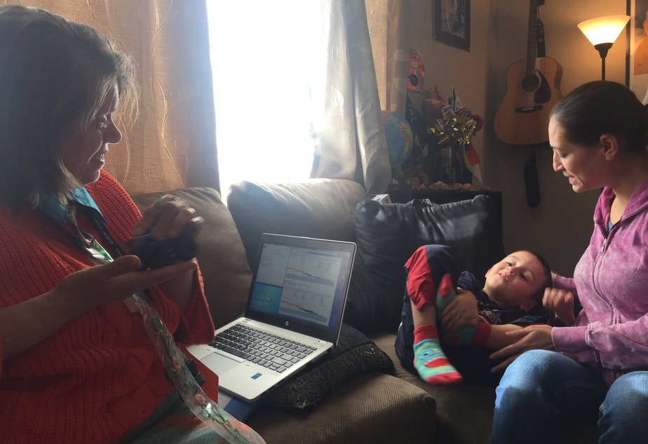 caption: GLEA family advocate Camille Churchill visits with four-year-old Moise, and his mother, Angela Madrid