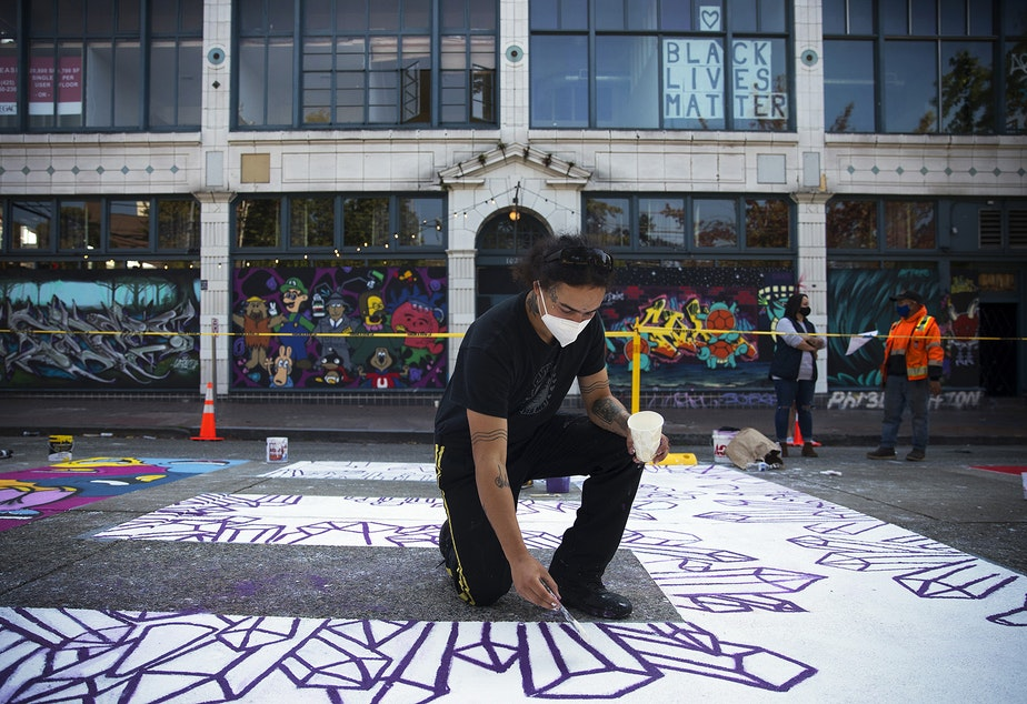 caption: Mixed media artist Future Crystals paints the letter E in the Black Lives Matter street mural on Friday, October 2, 2020, on E. Pine Street in Seattle.