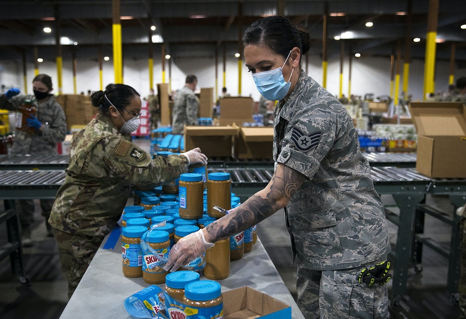 caption: Washington National Guard soldier Dahdia Hicks stacks jars of peanut butter on Tuesday, April 21, 2020, at a new emergency response center set up by Food Lifeline as a result of the growing need for food in Washington prompted by the coronavirus outbreak, along East Marginal Way South in Seattle. According to a Food Lifeline press release, the need has nearly doubled since the Covid-19 outbreak began while food donations have dropped by 70%.