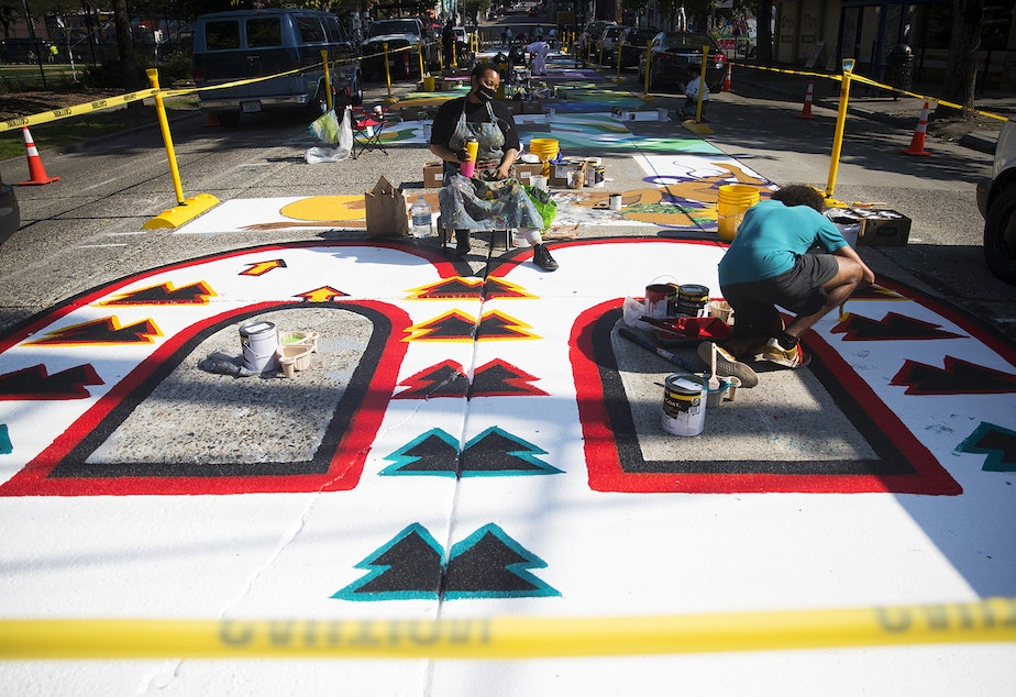 caption: Local artist Kimisha Turner, center, takes a break from painting the letter B in the Black Lives Matter street mural on Friday, October 2, 2020, on E. Pine Street in Seattle.