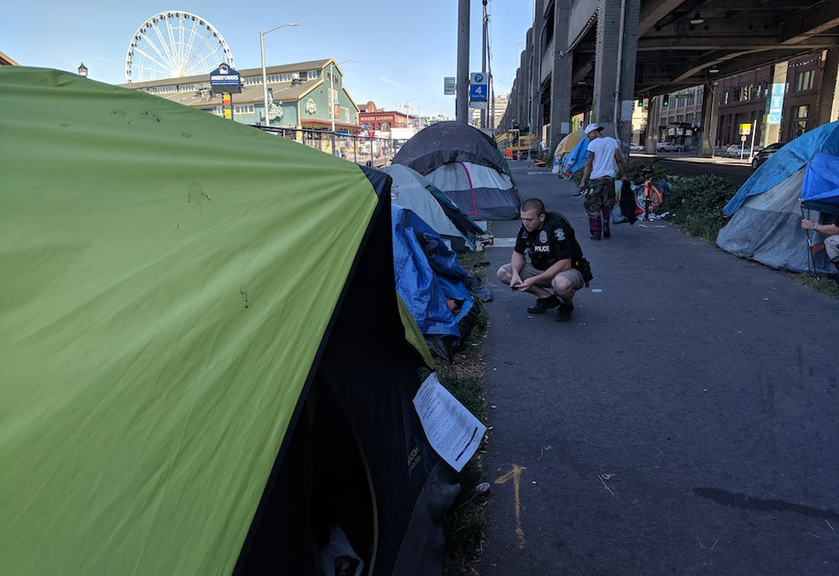 caption: Seattle Police Officer and Navigation Team member Brad Devore offers services and shelter to campers