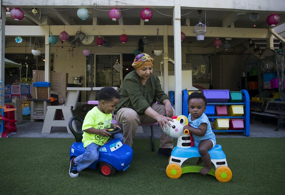 caption: Aqbal Kowaie, an overnight daycare employee, plays with 2-year-old Jaren Brown, left, and 10-month-old Avalon Brown, right, on Thursday, August 1, 2019, in Renton.