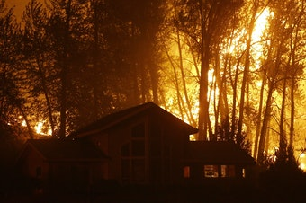 FILE: A wildfire burns behind a home on Twisp River Road early Thursday, Aug. 20, 2015 in Twisp, Wash.