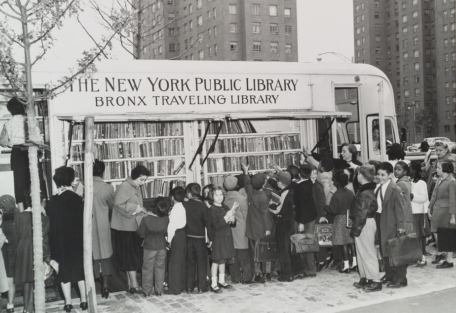 caption: Children in the Bronx visit a New York Public Library bookmobile in the 1950s. The institution turns 125 this year.