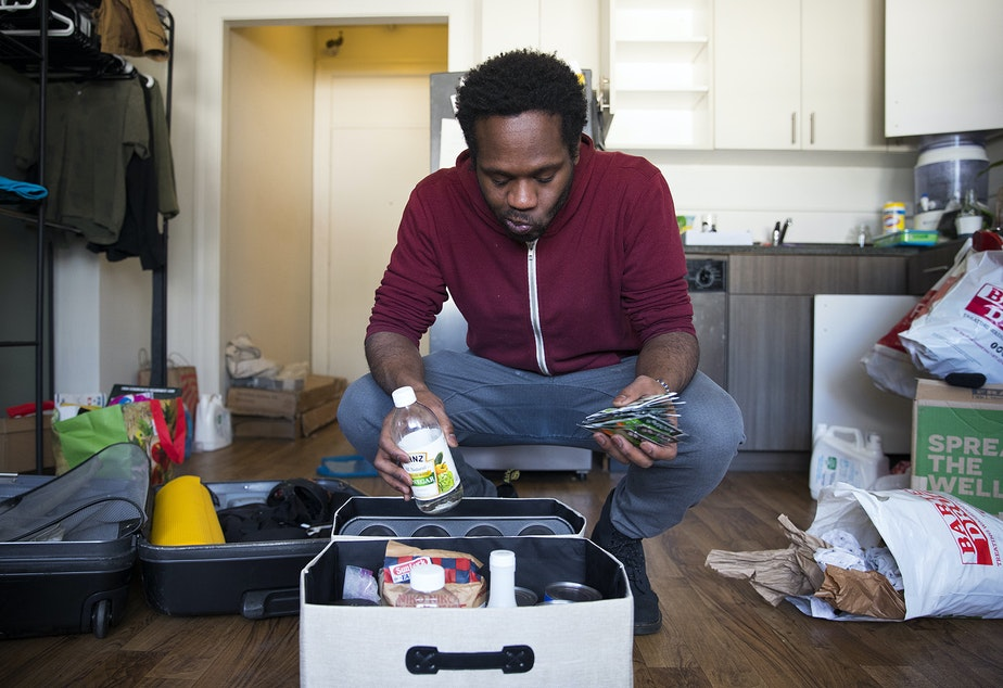 caption: Jordan packs his belongings at his studio apartment on Tuesday, February 26, 2019, after receiving an eviction notice, on 4th Avenue South in Seattle.