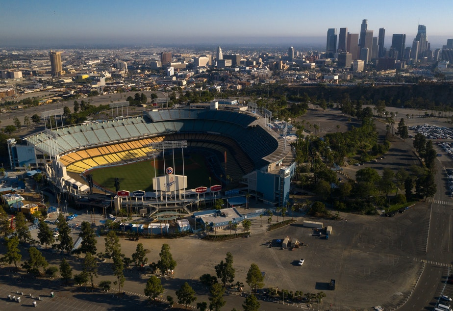 caption: Dodger Stadium in Los Angeles stands empty in an aerial view from late May. Games will resume in late July.