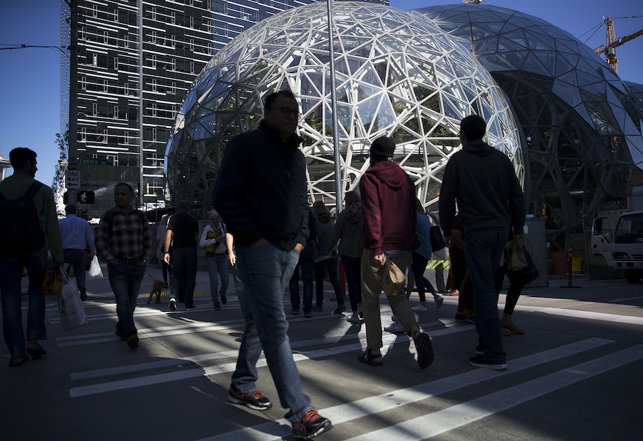 caption: Pedestrians cross the street at Amazon headquarters in Seattle in September.