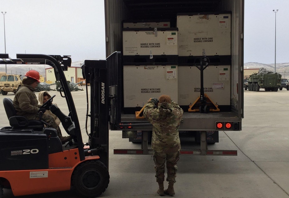 caption: Washington National Guard Members unloading medical supplies