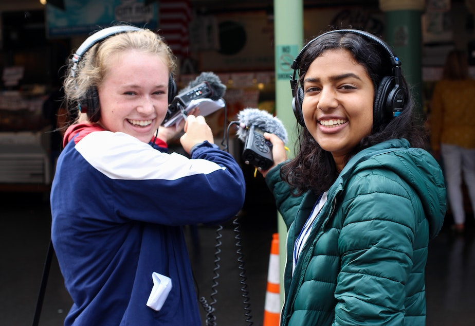 caption: Morgen White and Ritika Managuli pose while collecting ambient sound at Pike Place Market for an interviewing exercise during the 2019 Intro to Radio Journalism Workshop.