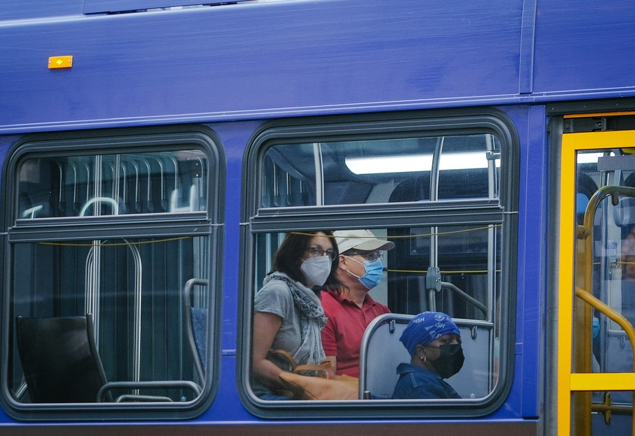 caption: Masked passengers ride the bus through downtown, August 3, 2021. Masks remain a requirement on King County public transit, including busses and street cars.