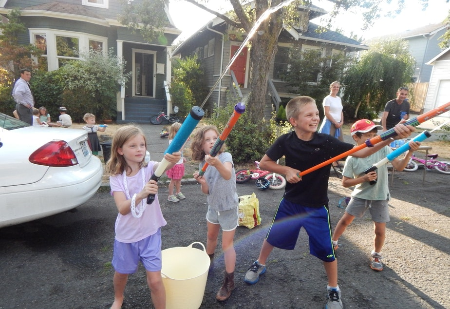 caption: Kids play on a closed street in Seattle's Central District. Water was the theme here.