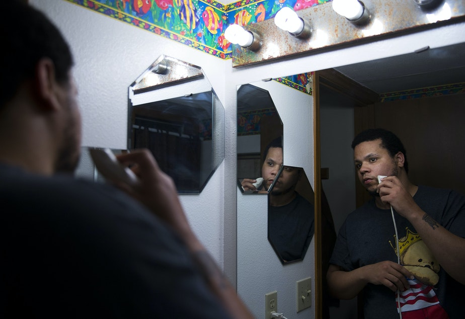 caption: DaShawn Horne looks in the mirror while shaving on Thursday, November 15, 2018, the night before Julian Tuimauga's sentencing, at his home in Auburn.