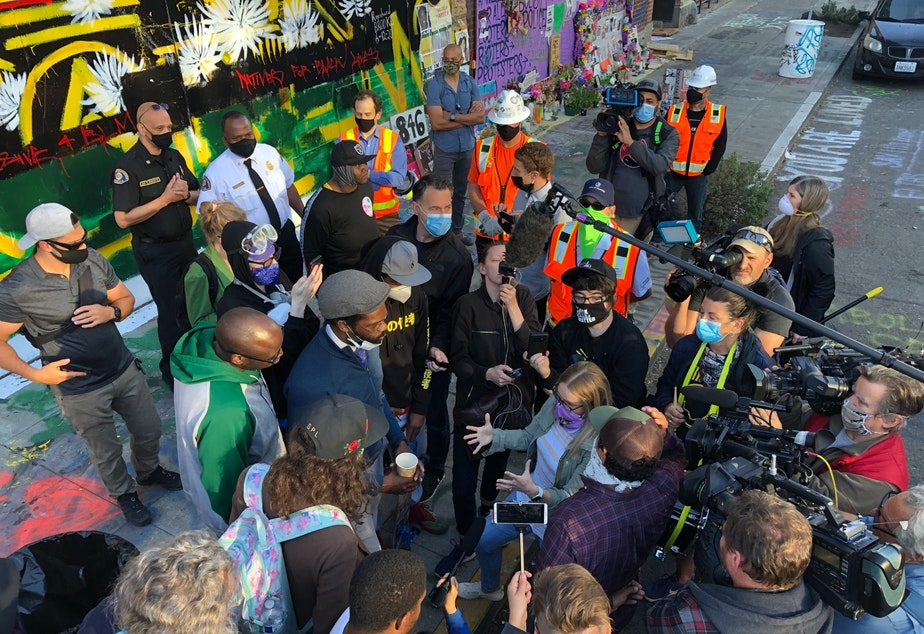 caption: Mayor Jenny Durkan's Chief of Staff, Stephanie Formas, speaks with protester David Lewis after protesters confronted city workers who tried to clear barriers at 5:30 AM on June 26, 2020. Also present is Fire Chief Harold Scoggins and SDOT head Sam Zimbabwe.