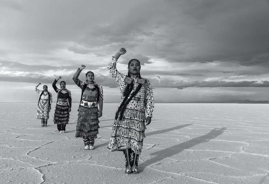 caption: From front, Erin Tapahe, JoAnni and Sunni Begay and Dion Tapahe pose with their fists raised on the Bonneville Salt Flats in northwestern Utah.