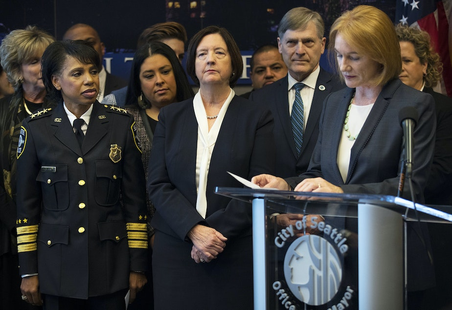caption: FILE: Then-deputy Chief Carmen Best, left, and then-Seattle Police Chief Kathleen O'Toole listen as Mayor Jenny Durkan speaks during a press conference on Monday, December 4, 2017, at Seattle City Hall.