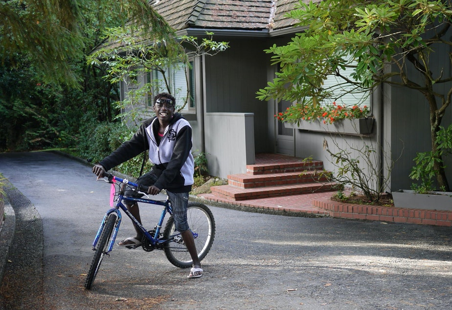caption: Mario, an 18-year-old refugee from Eritrea, outside his host home in Burien. Mario and his siblings each picked out a bike of their own, thanks to a donation to World Relief.