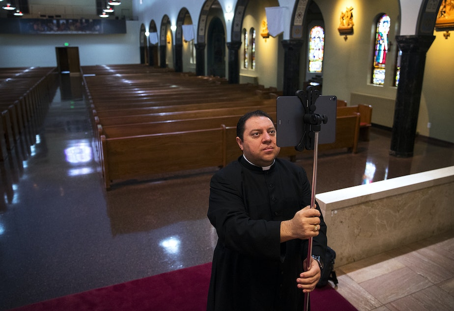 caption: Father Jose Alvarez sets up an iPad ahead of a live-streamed daily mass in Spanish on Friday, April 24, 2020,  at Holy Family Roman Catholic Church in White Center.