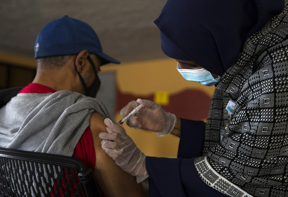 caption: Registered nurse Hamdi Abdi, right, administers the first dose of the Moderna Covid-19 vaccine for Charles Jackson, left, on Wednesday, February 3, 2021, during a vaccine clinic set up by the Somali Health Board in partnership with the Othello Station Pharmacy and Brighton Apartments to vaccinate 100 seniors in the community on at the apartment complex along Rainier Avenue South in Seattle.