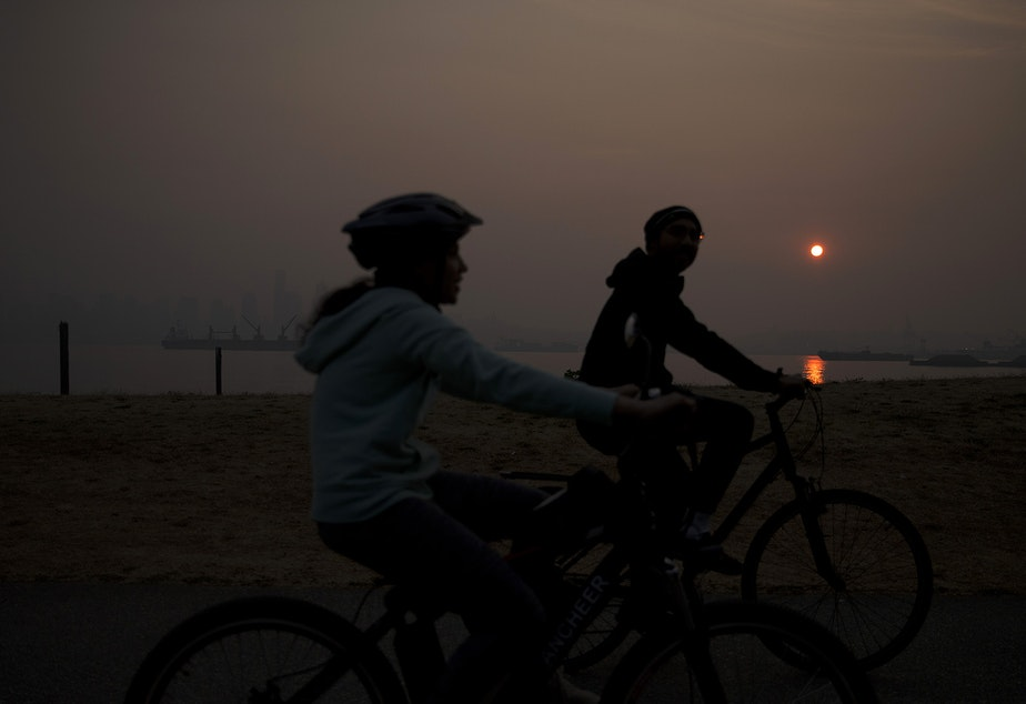 caption: Cyclists ride along Harbor Avenue Southwest as the sun rises over a smokey Seattle on Friday, September 11, 2020. A massive plume of smoke from wildfires burning in California and Oregon made it's way into the area overnight on Thursday.